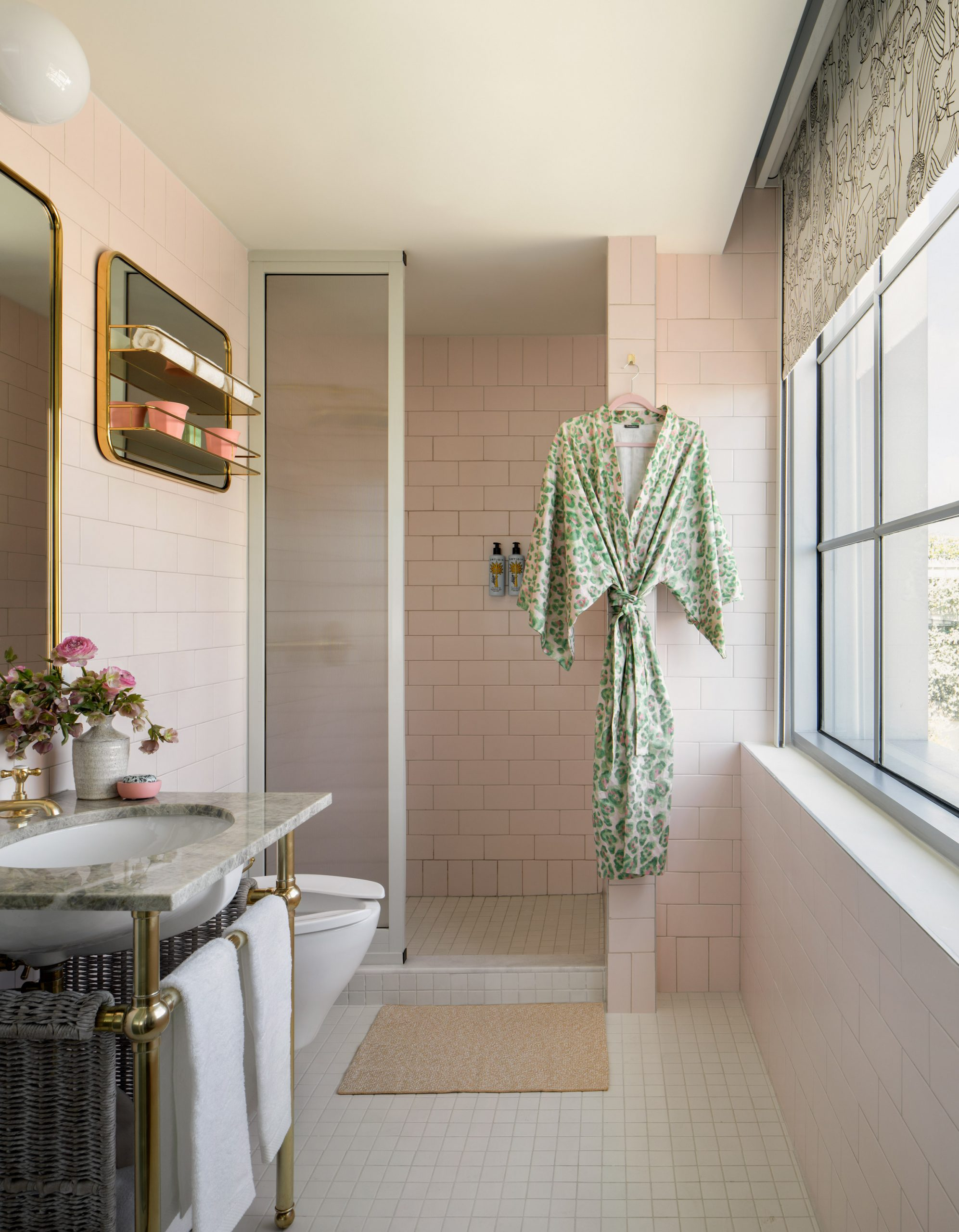 Bathroom in Goodtime Hotel with brass and green stone sink and light pink tiles