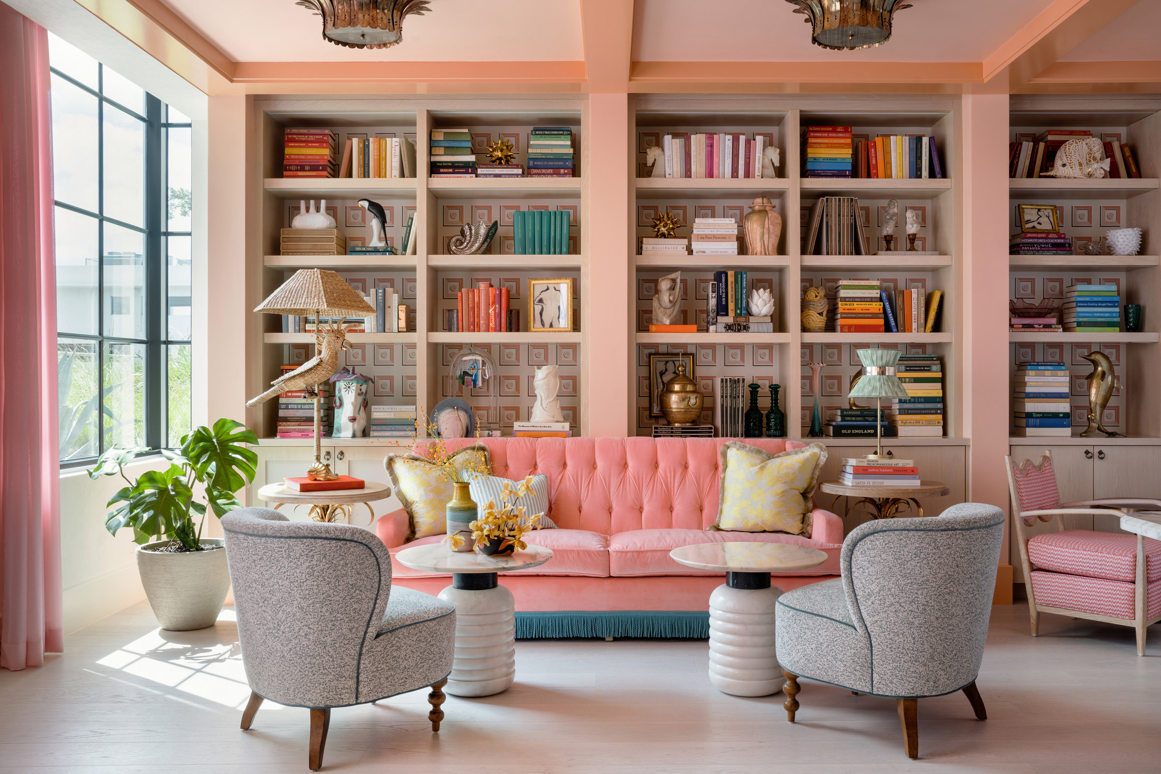 Library of the Goodtime Hotel with pink couch and built-in bookshelves