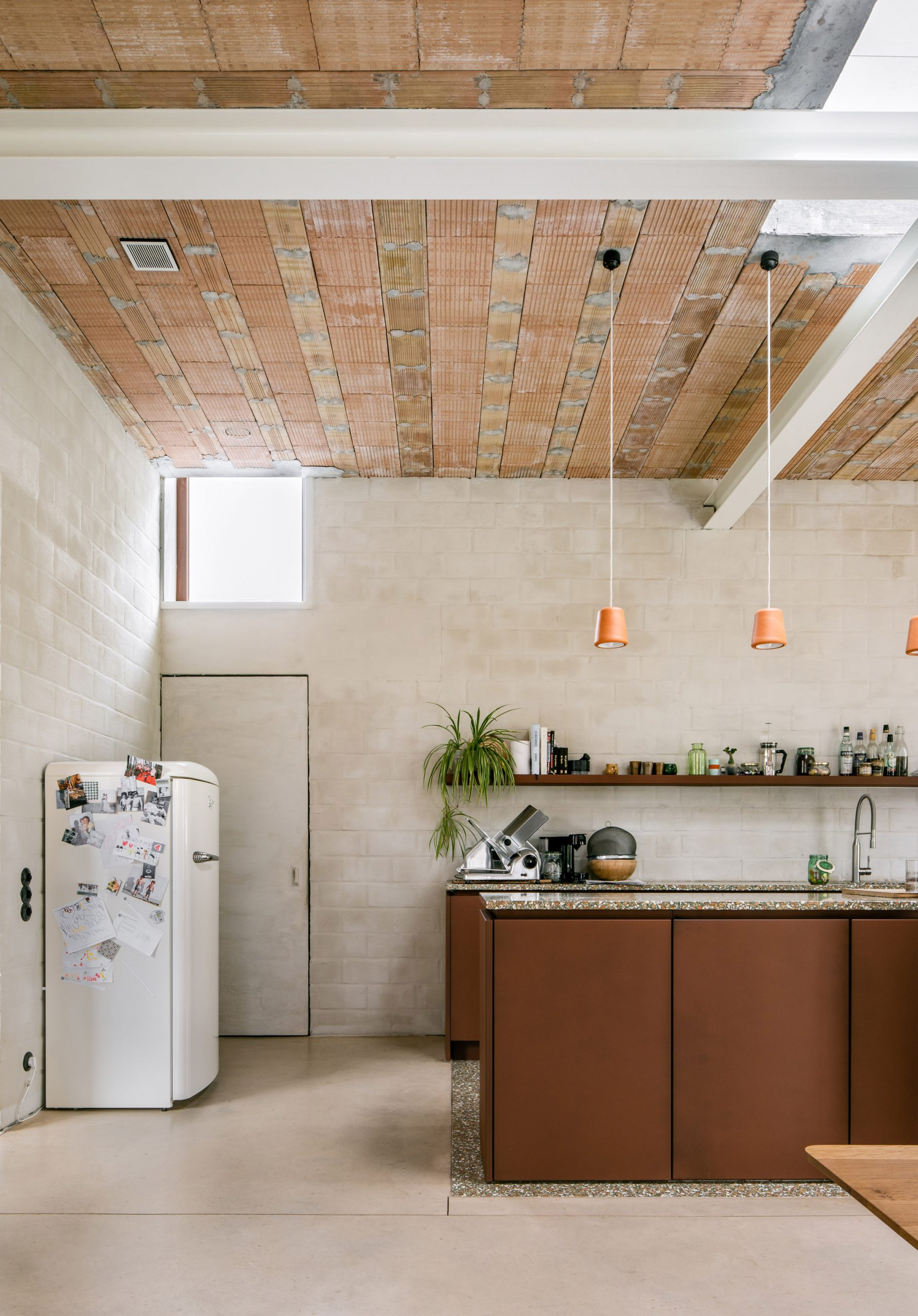 A kitchen with a tall ceiling and rough plaster walls